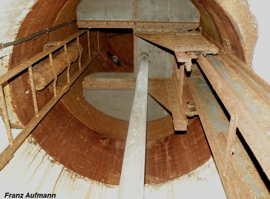 Fot. 4. Widok podestu w szybie kopuły obserwacyjno– bojowej model 1929 typ A.. Od lewej: rura napowietrzająca, drabina , podest z włazem, rura zrzutni łusek, dźwigary podestu .
