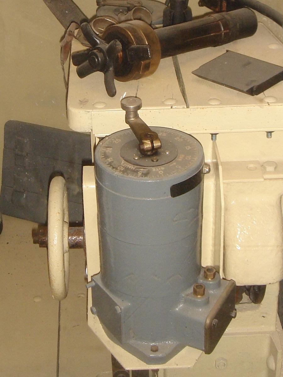 """Fot. 4. Przyrząd do płynnego sterowania położeniem reflektora w jednej z dwóch płaszczyzn. Był mocowany do stalowych półek po obu stronach pulpitu, znajdującego się nad dźwigarem. platformy Zdjęcie wykonane w muzeum dużej grupy warownej """"Fermont""""."""