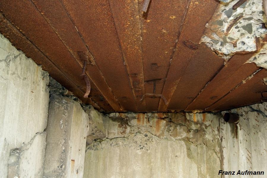 Fot. 039. Strop lewej izby bojowej. Uchwyty do mocowania rur układu odprowadzania gazów prochowych. W głębi po prawej stronie rura osadzona w ścianie do odprowadzania gazów prochowych na zewnątrz schronu.