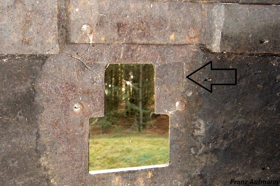 Fot. 03. Widok otworu strzelnicy gazoszczelnej kopuły Z.O. według projektu z 1937 roku. W górnej części znajdują się cztery gwintowane otwory do mocowania zamknięcia. Strzałką zaznaczono cylindryczne wgłębienie charakterystyczne dla zastosowanego zamknięcia górnej części strzelnicy.