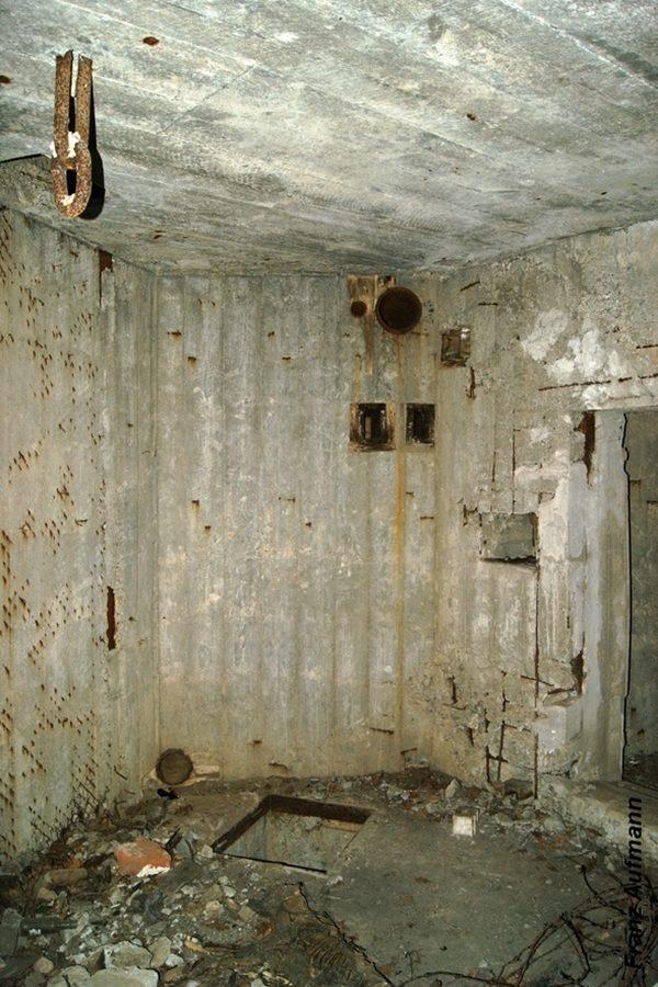 Fot. 12. Widok maszynowni od strony fundamentu na generator prądotwórczy. Nad fundamentem mocowano w stropie jarzmo, pomocne w ustawianiu generatora lub jego przeglądach. W głębi w ścianie osadzone rury do usuwania gazów spalinowych i zanieczyszczonego powietrza. Poniżej otwory o przekroju czworokąta do osadzenia wsporników pod wentylator.