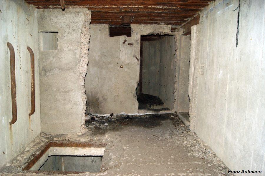 Fot. Pomieszczenie na skład amunicji i szyb łączący obie kondygnacje. W głębi wejście do izby bojowej. Za szybem zniszczona ściana działowa pomieszczenia dowodzenia.