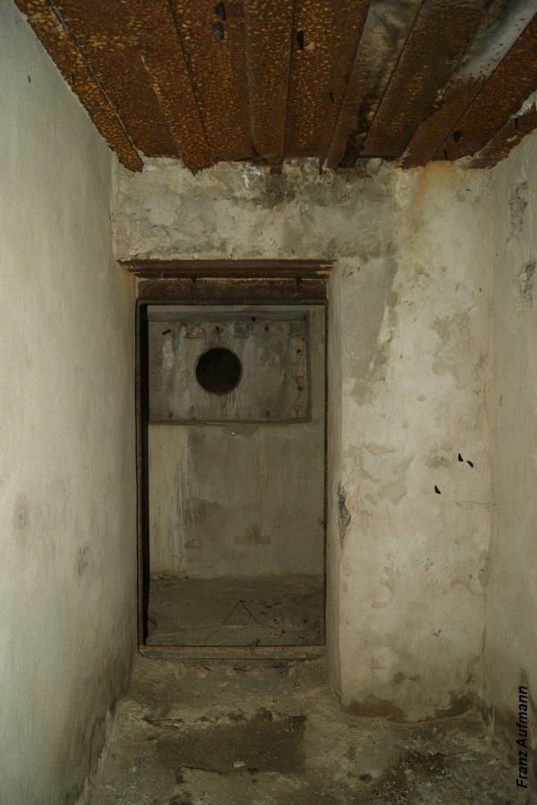 Fot. Śluza przeciwgazowa. Widok od strony korytarza w kierunku wejścia do schronu. W głębi nisza czerpni powietrza.