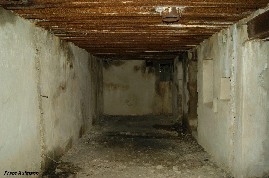 Fot. 05. Widok od strony izby bojowej dla stanowiska Ł-17 w kierunku izby załogi. Nie wykonano dwóch ścianek działowych wydzielających izbę dowodzenia i skład amunicji. Na pierwszym planie pancerz peryskopu, osadzony w stropie schronu.