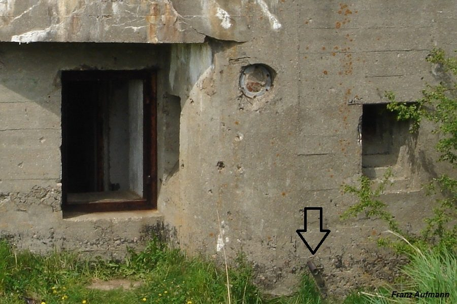 Fot. Widok tylnej elewacji schronu z zaznaczonym położeniem rurki odprowadzającej ścieki.