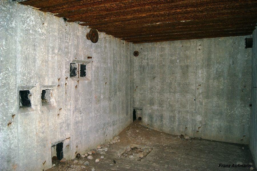 Fot. 11. Widok w kierunku zaplecza technicznego schronu. Nie wykonano ścian działowych. Poniżej stropu wlot rury usuwającej zanieczyszczone powietrze na zewnątrz schronu. Było tłoczone przez wentylator, który miał być zamocowany do dwóch wsporników, osadzonych w ścianie.