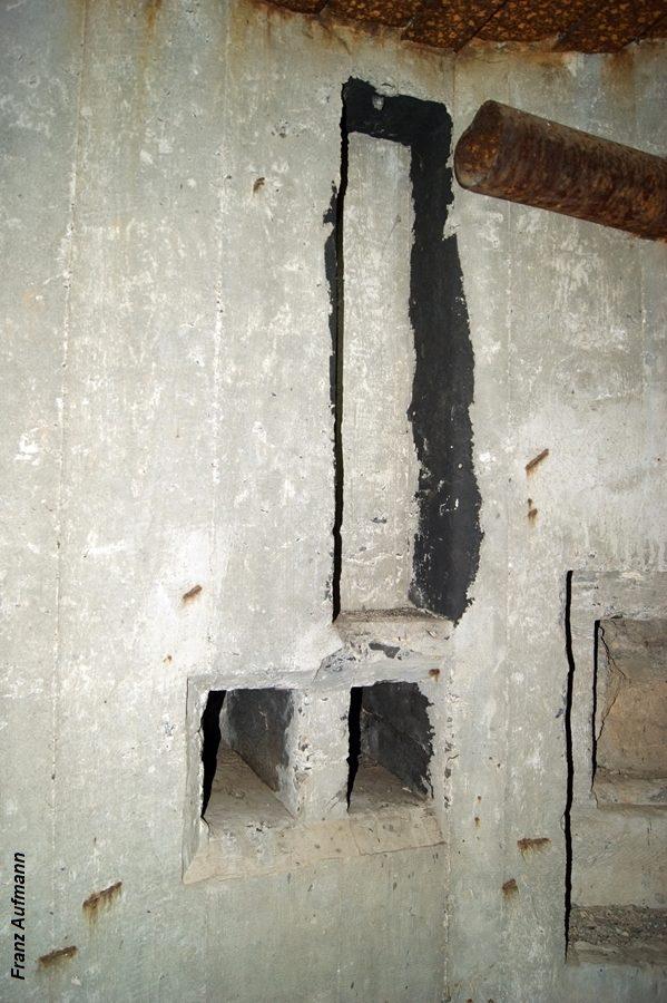 Fot. 06. Otwory na wsporniki pod wentylator układu usuwania gazów prochowych i pionowy kanał w ścianie na rurę doprowadzającą gazy do wentylatora. U góry, po prawej stronie rura odprowadzająca gazy na zewnątrz schronu.